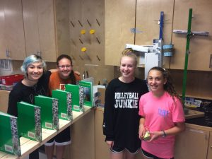 Marley, Brooke, Kendall, and Emily start the machine in action by burning a candle.